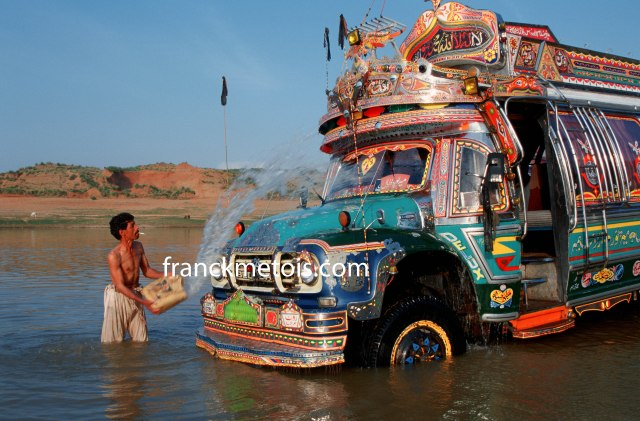 Helper washing a bus. Pakistan